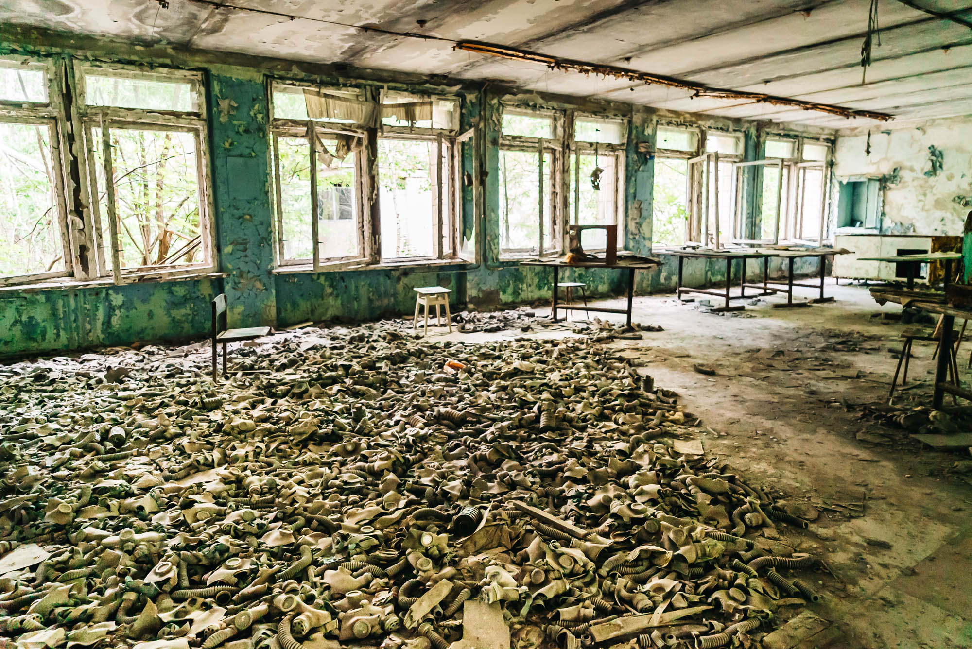 Hundreds of children's gas masks laying on the floor of an abandoned school in Pripyat