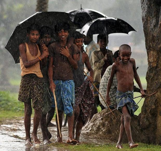 Children walk along a muddy hillside in Nepal, smiling in the rain.