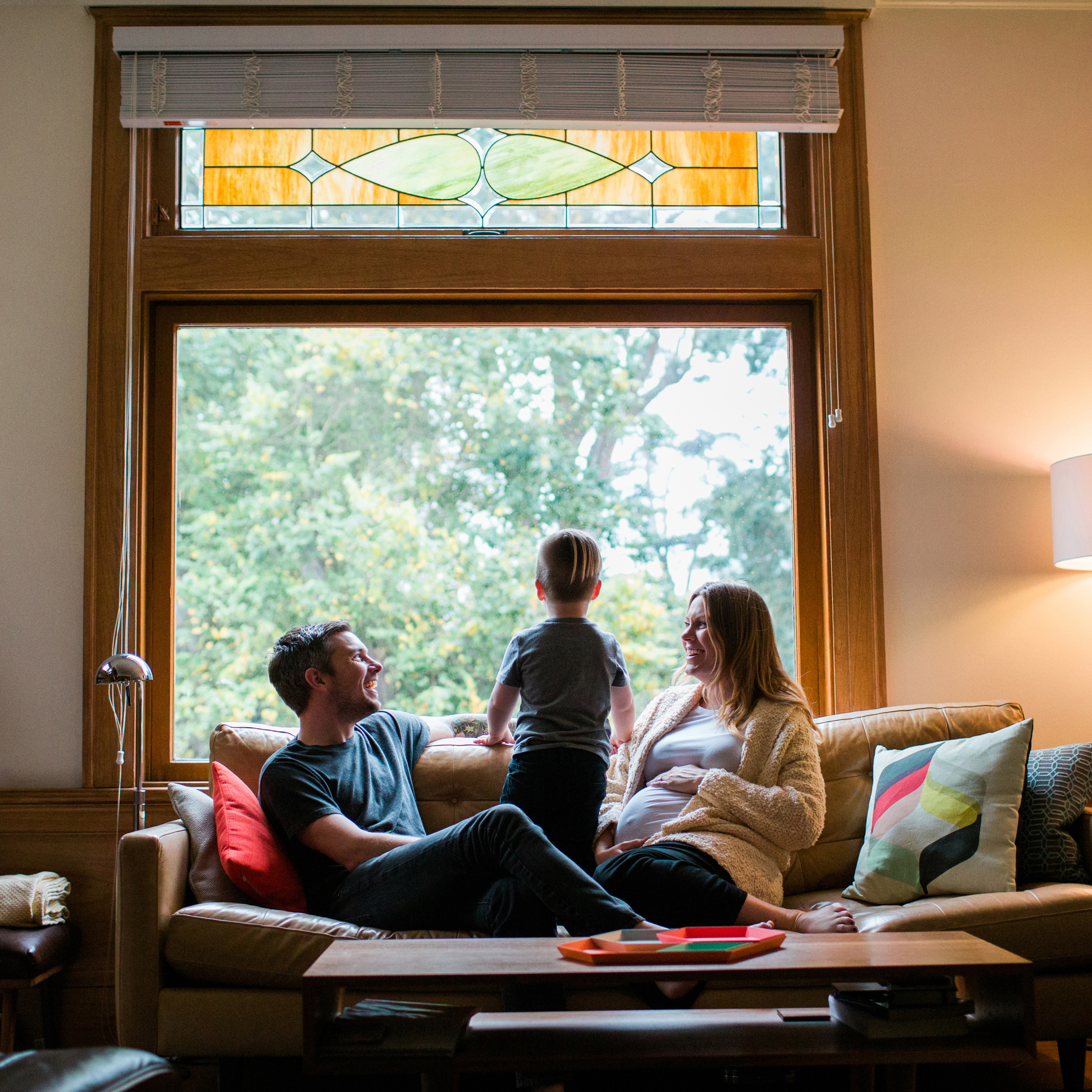 family at home pregnant mom two year old boy sitting on couch.jpg