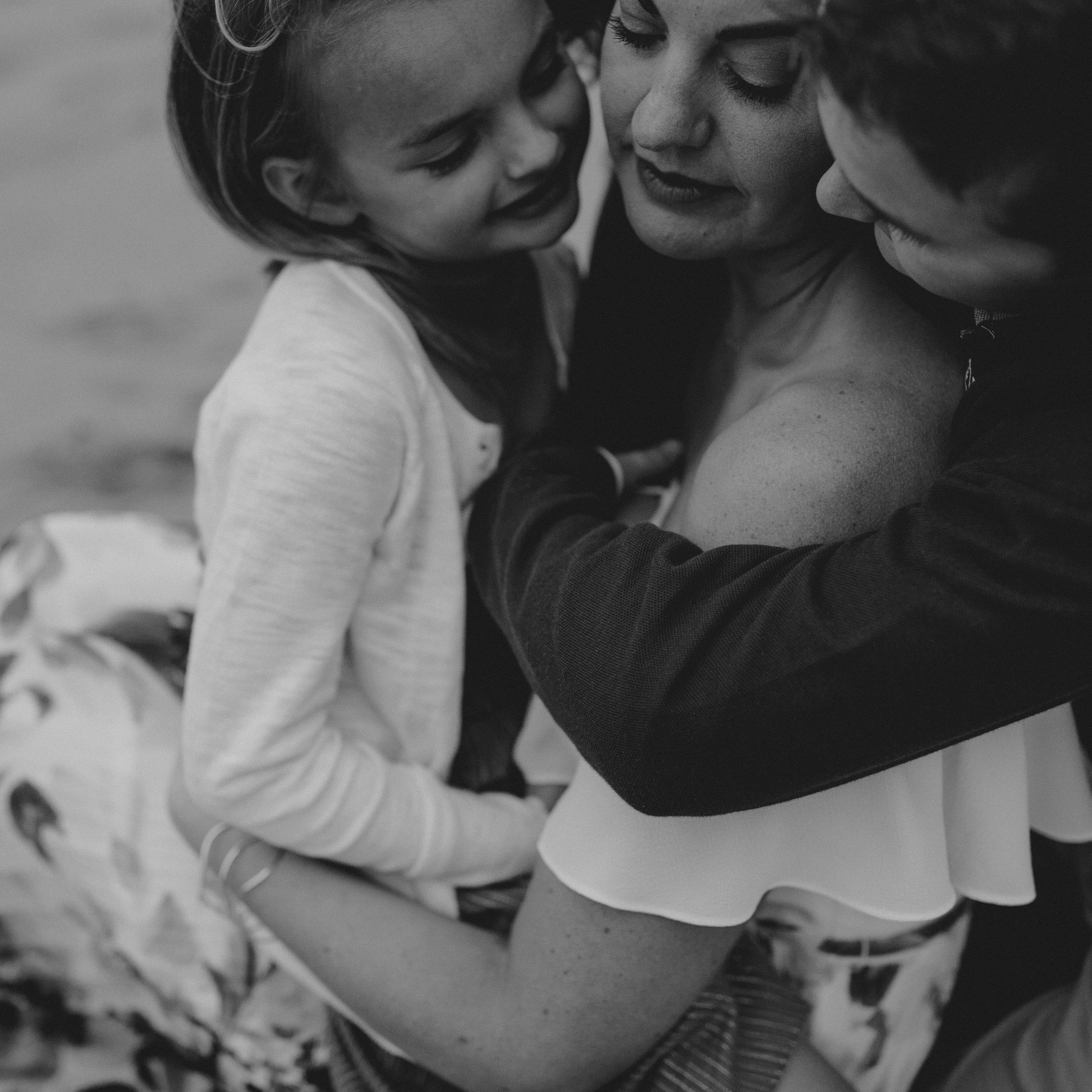 pretty mom with son and daughter giving snuggles and love black and white family photo.jpg