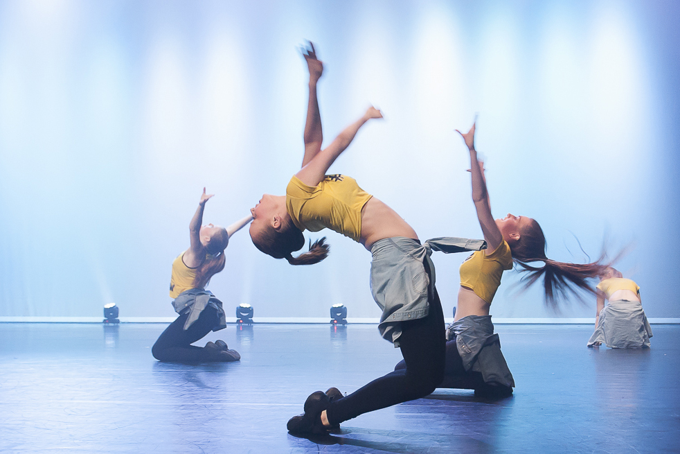 Dancers on their kness reaching upwards while bending over backwards