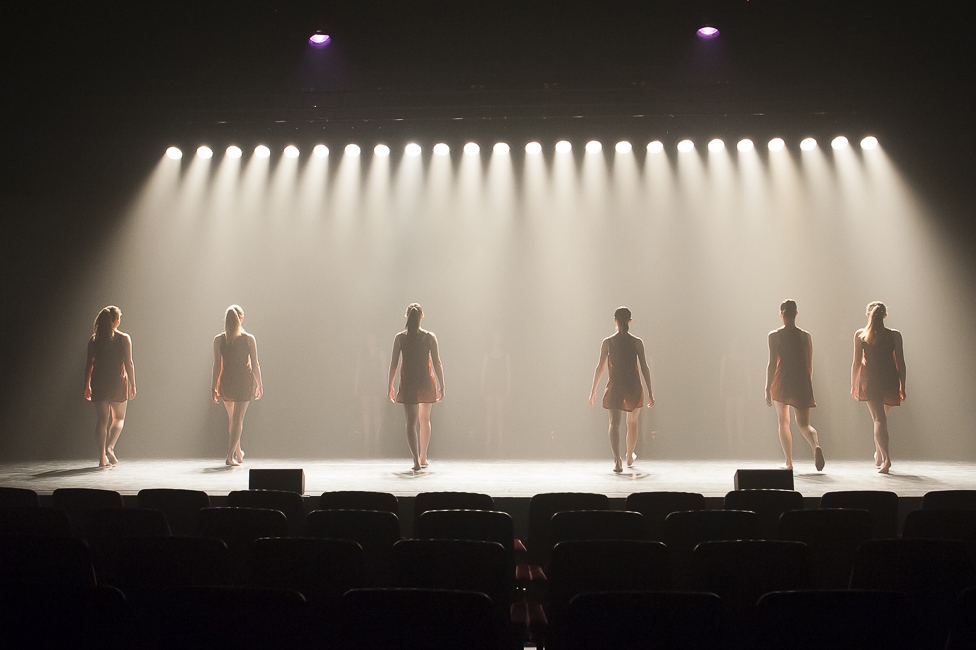 Dancers facing back with stage lights