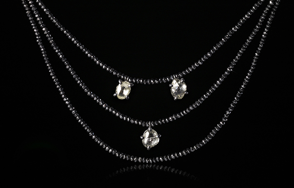 Showpiece collier with rows of black polished diamonds and raw diamonds.