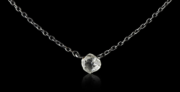 Raw round diamond hovering in black white gold chain necklace.