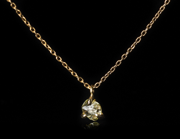 Petite yellowish diamond on a gold chain necklace.