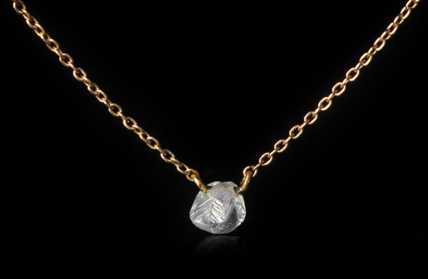Dangling petite raw diamond on a gold chain necklace.