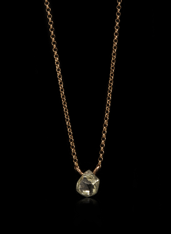 Alluvial Greenish rough diamond dangling on a rose gold necklace.