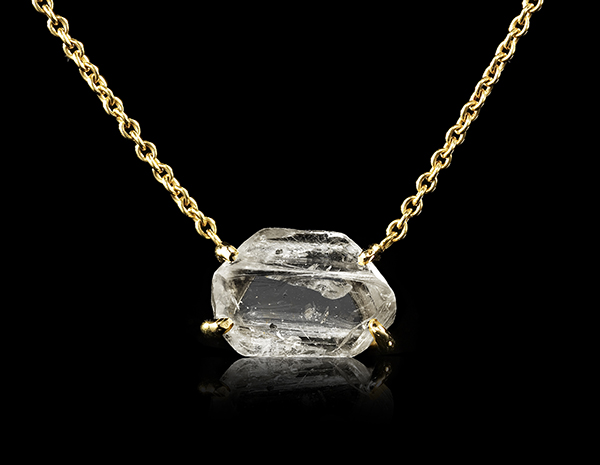 Rough diamond with inclusions and feathers on a gold necklace.