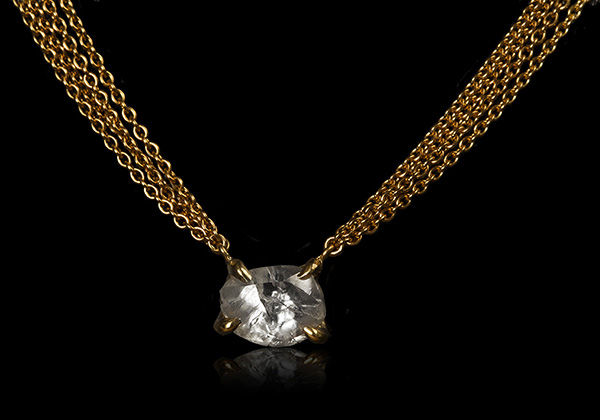 Oblong whitish diamond necklace sitting close to the neck.