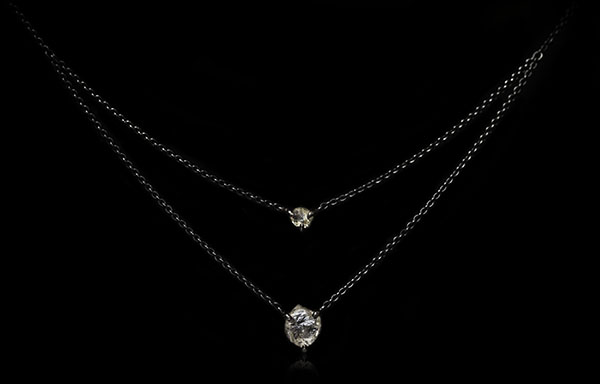 Two diamonds dangling on a two chain black necklace.