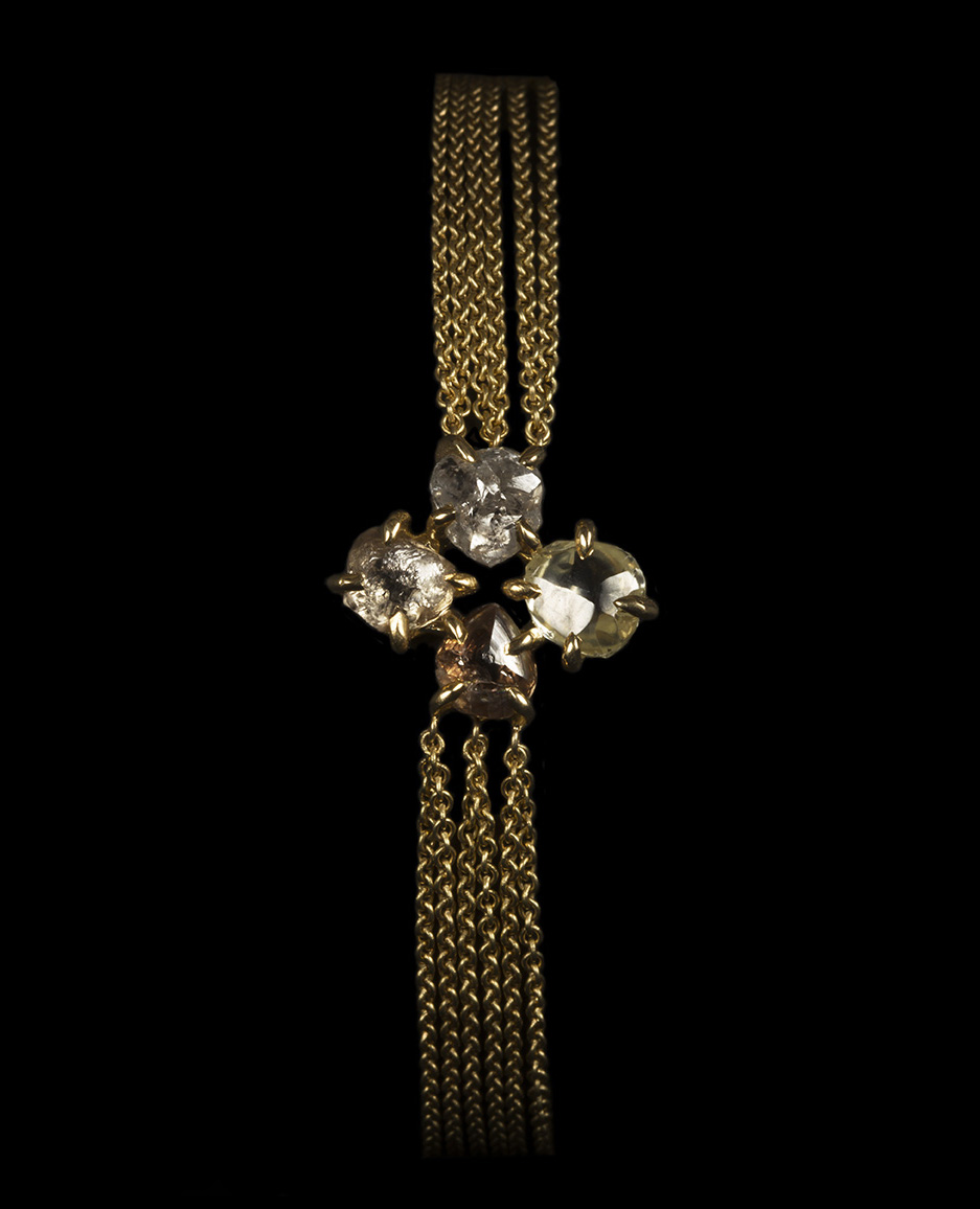 Rough diamonds in four leaf clover shaped gold bracelet.