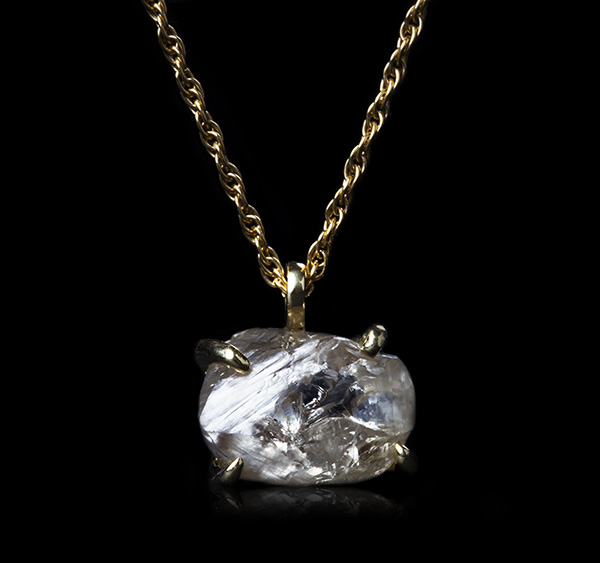 Large white raw diamond suspended as a pendant on a necklace.