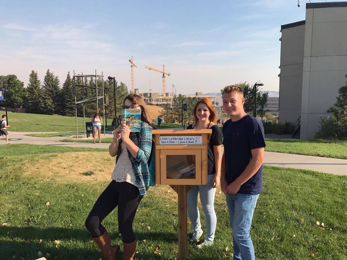 Kaleigh (left), Emily (middle), and Spencer (right), posing next to the Little Lethbridge Library in the bus loop. They were all very happy to cross another item off their scavenger hunt checklist!