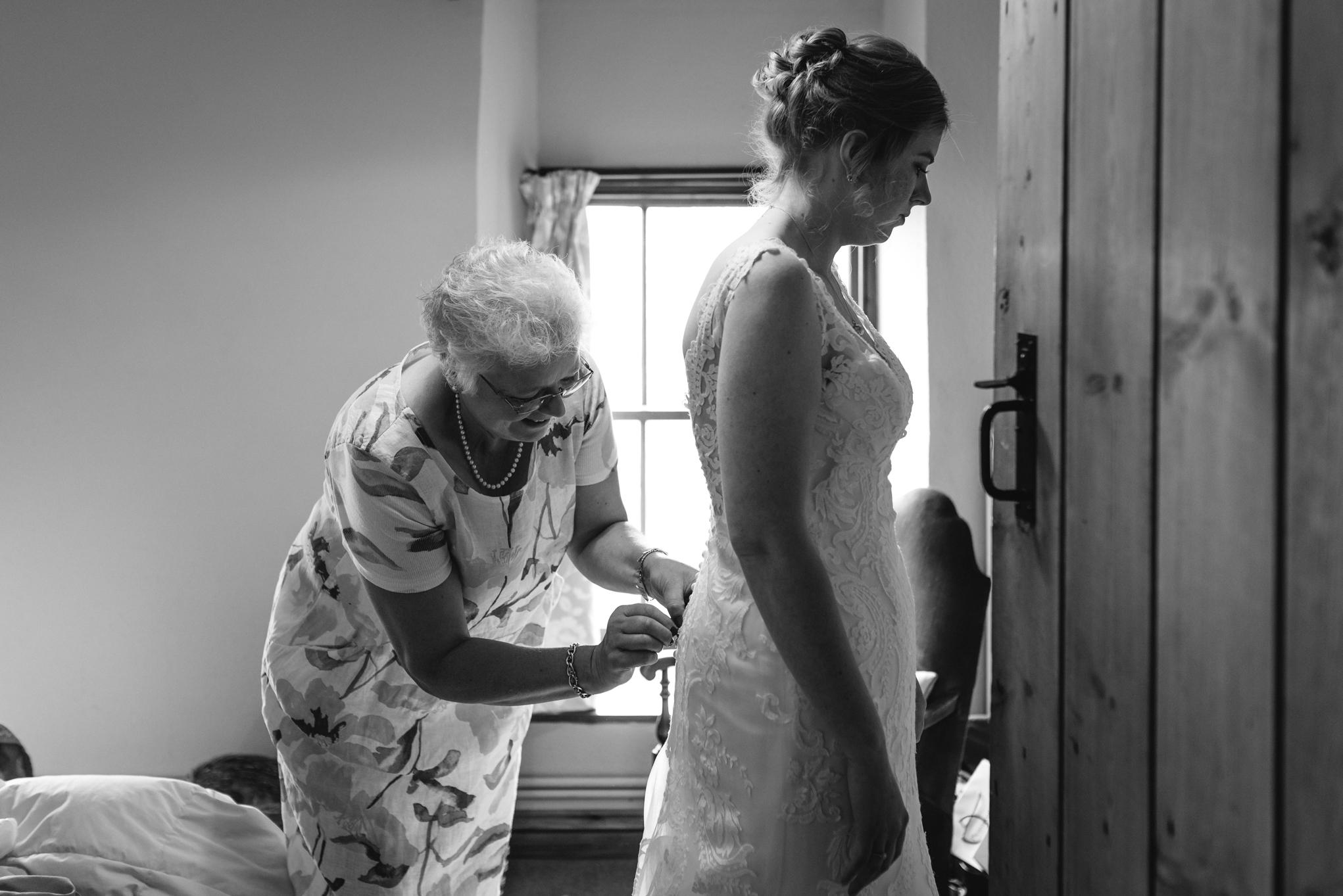 Bride having wedding dress done up - Powys Wedding Photography