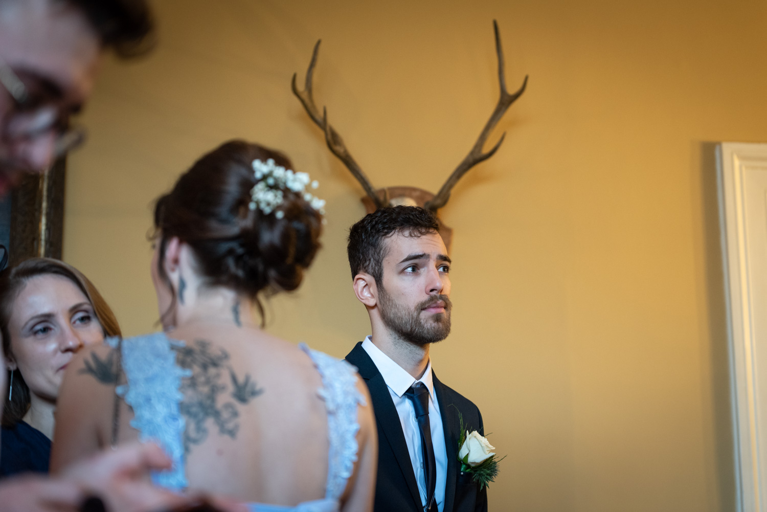Man stood in front of antlers