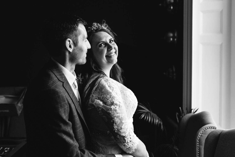 bride and groom in front of window