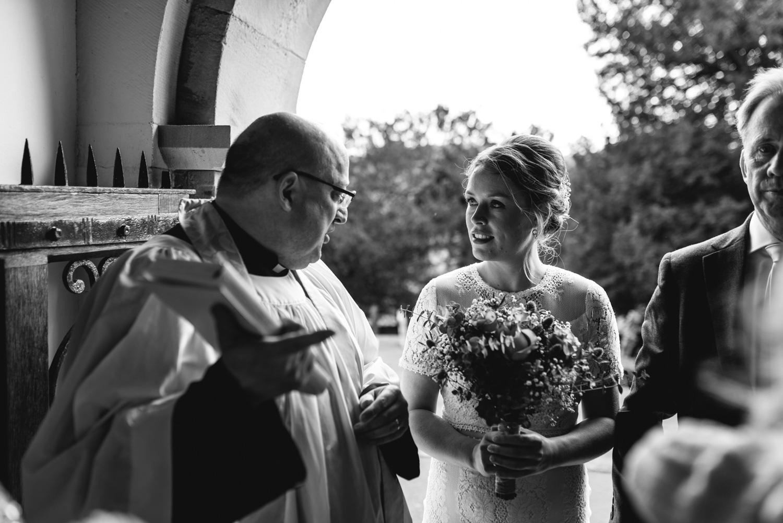 Bride talking to vicar at church