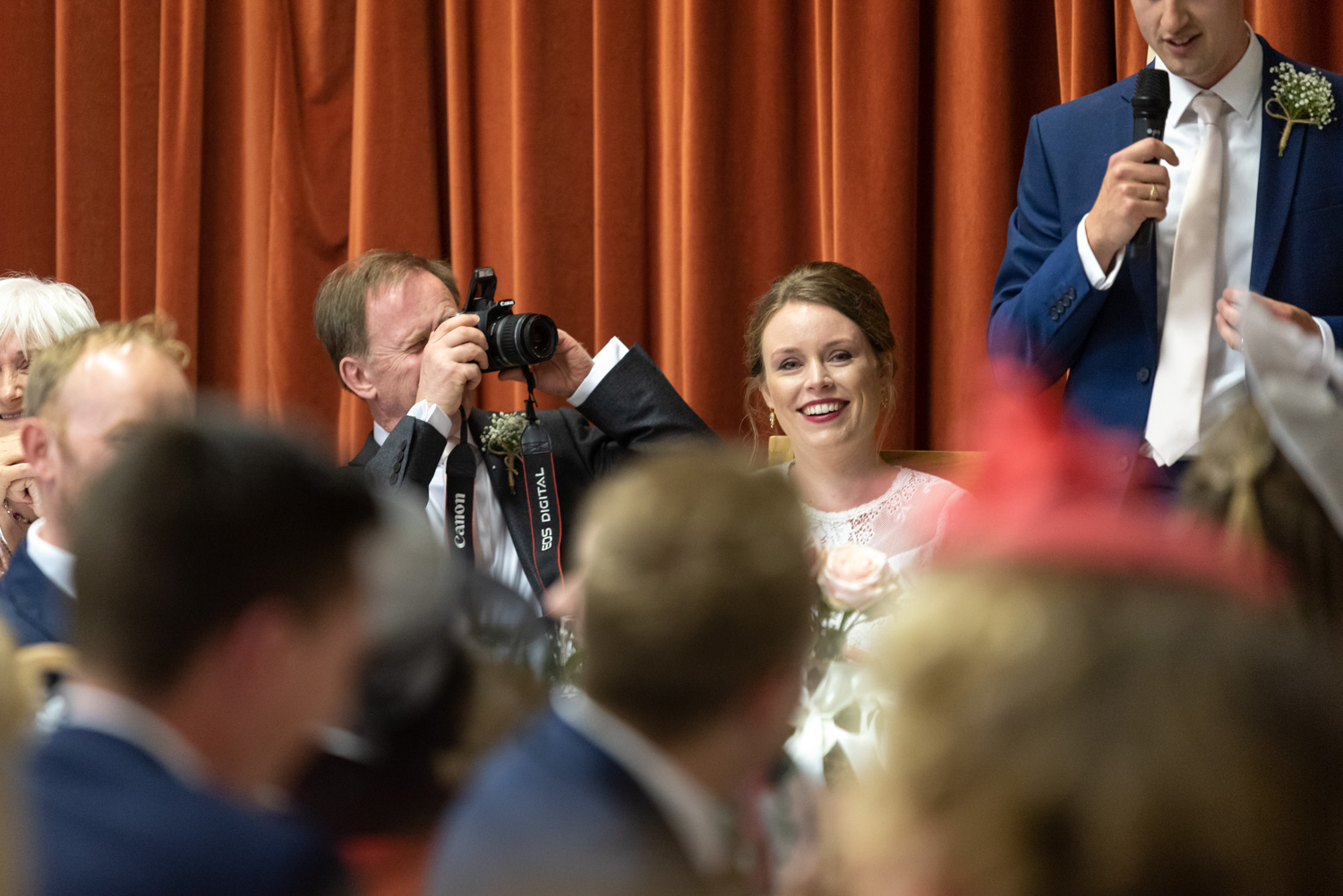 Brides father taking photo during grooms speech
