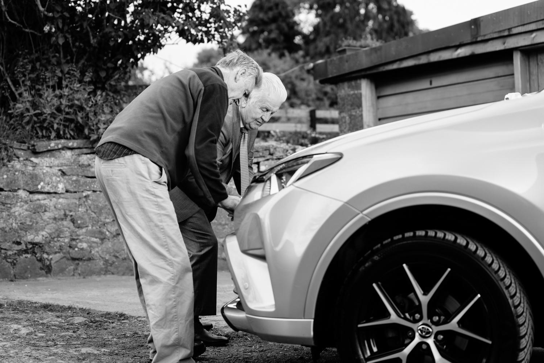 Two old men tying ribbon to car