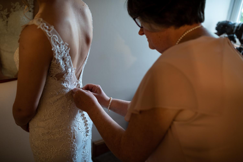 Mother doing back of brides dress up