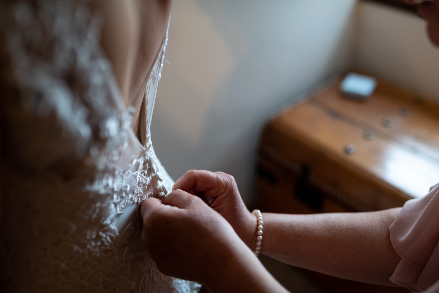 Close up of brides dress being done up