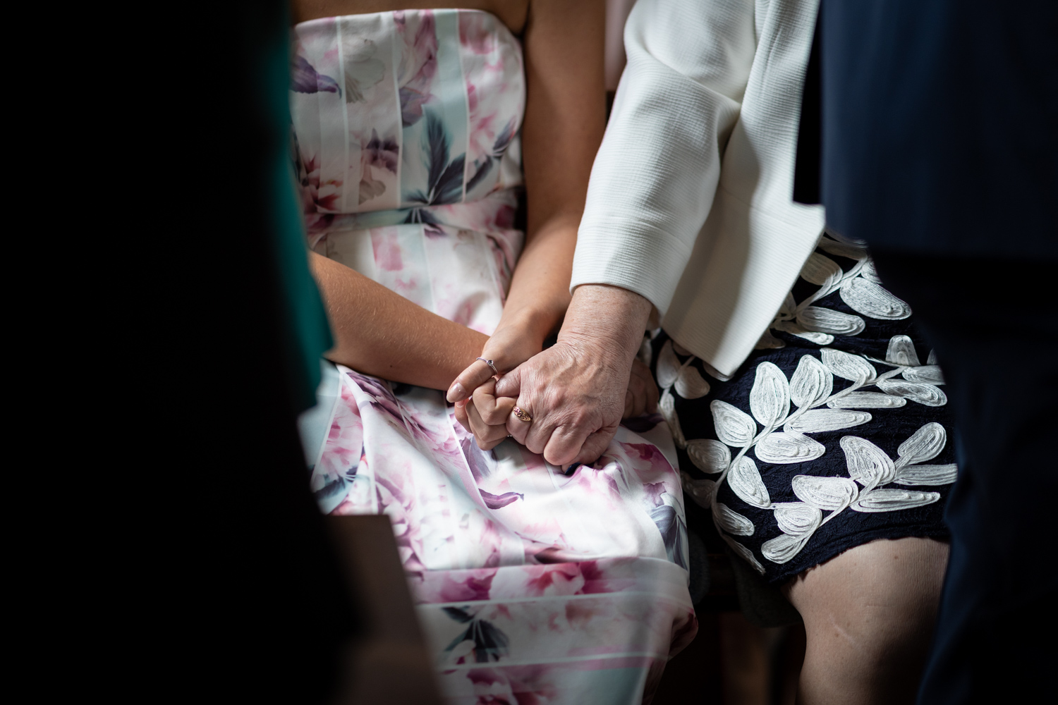Mother of groom holding hands with granddaughter