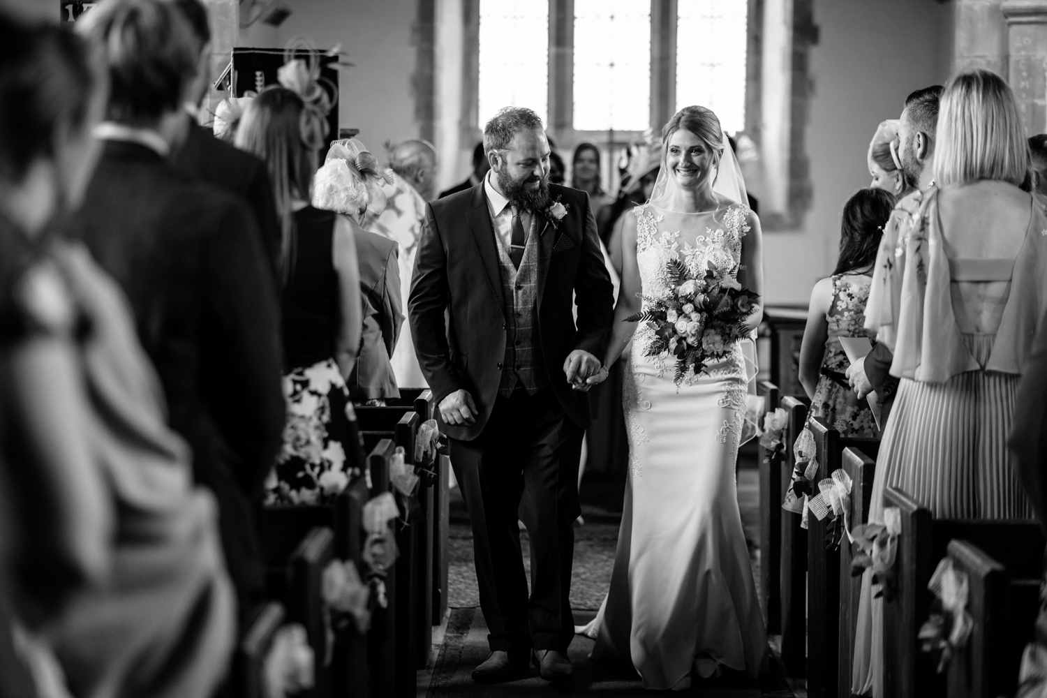 Bride and groom walking out of church up the aisle