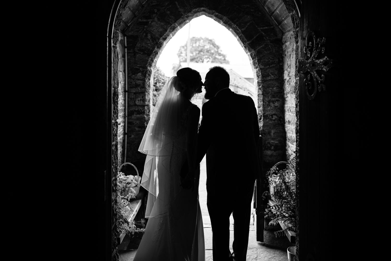Bride and groom kiss in church doorway