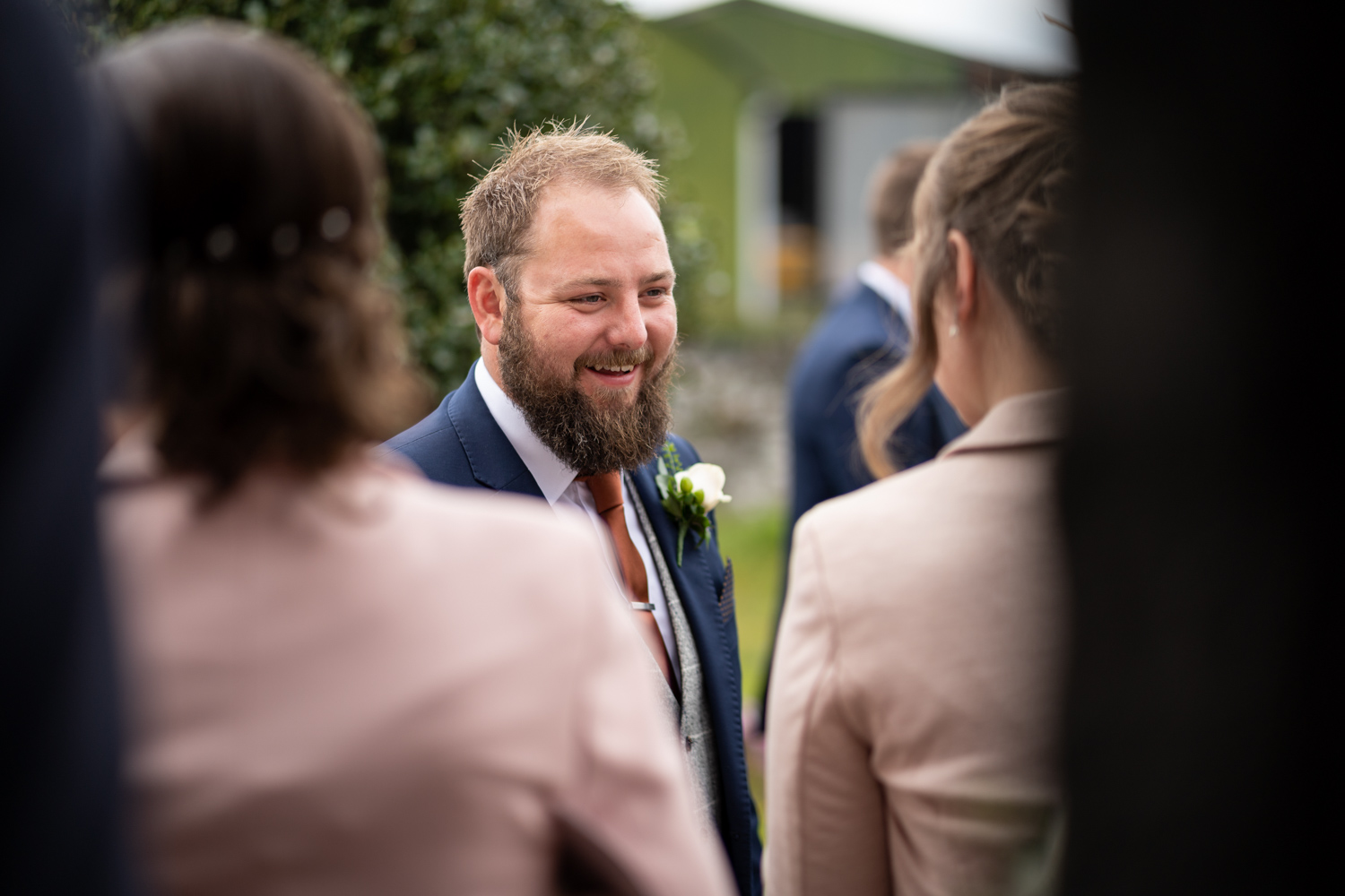 Groom talking to guests outside church