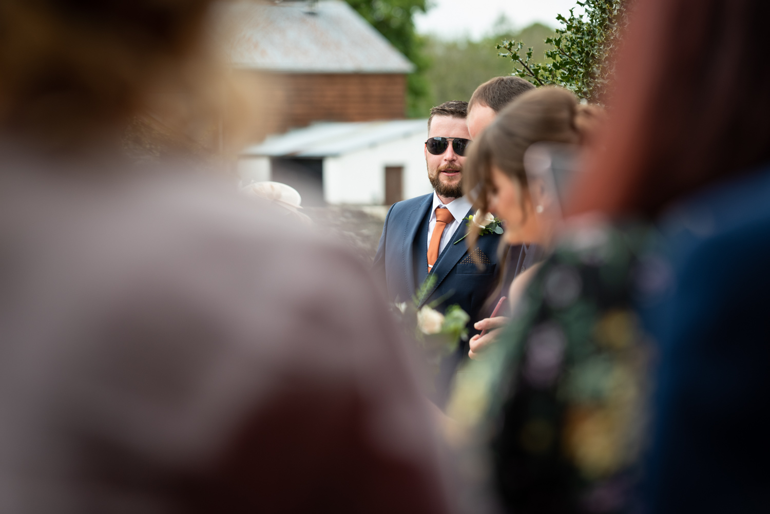Best man talking to other wedding guests