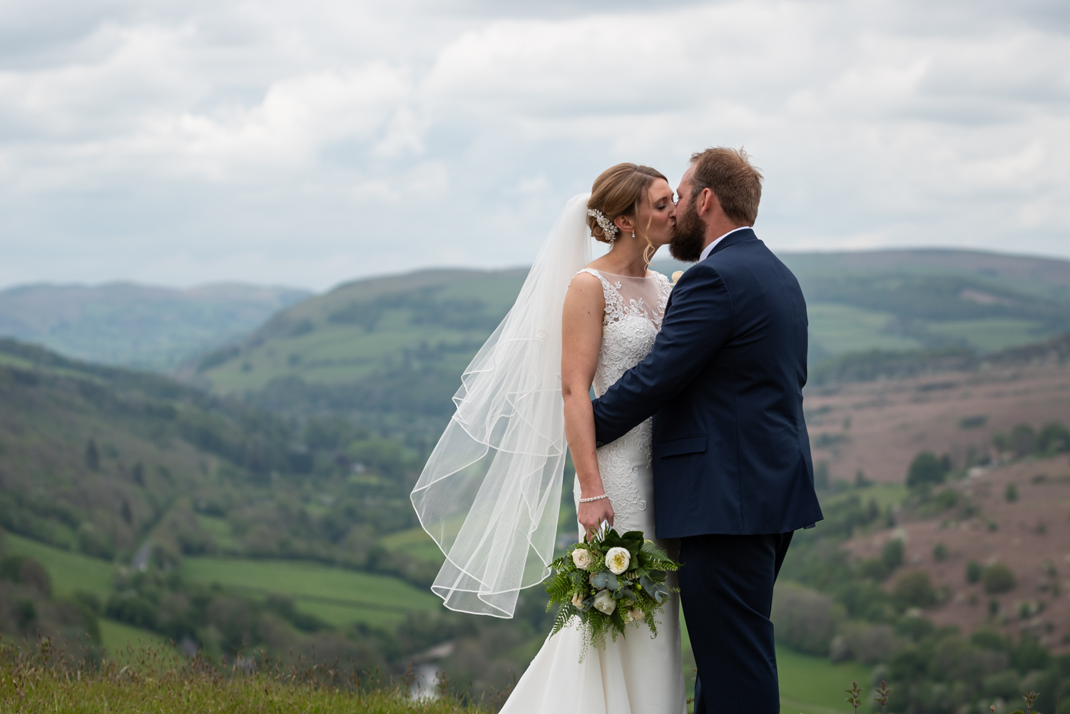 Bride and groom kiss with stunning countryside backdrop