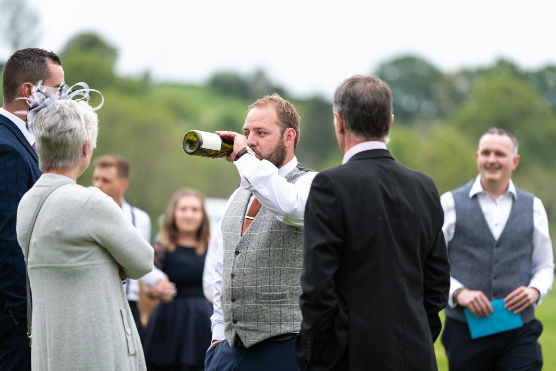 Groom drinking from wine bottle
