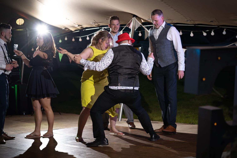 Two wedding guests dancing