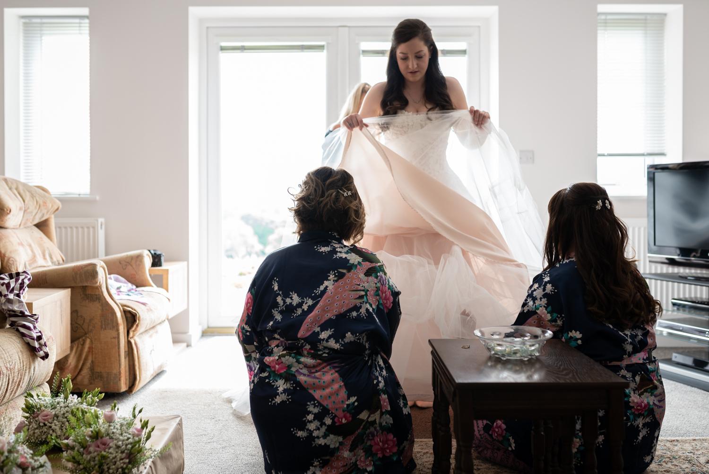 Bridesmaids under brides dress