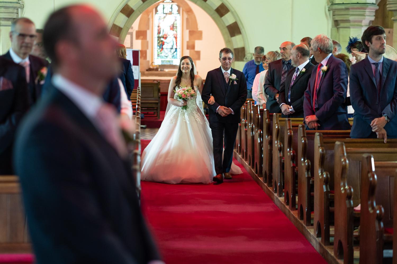 Bride walking down church aisle
