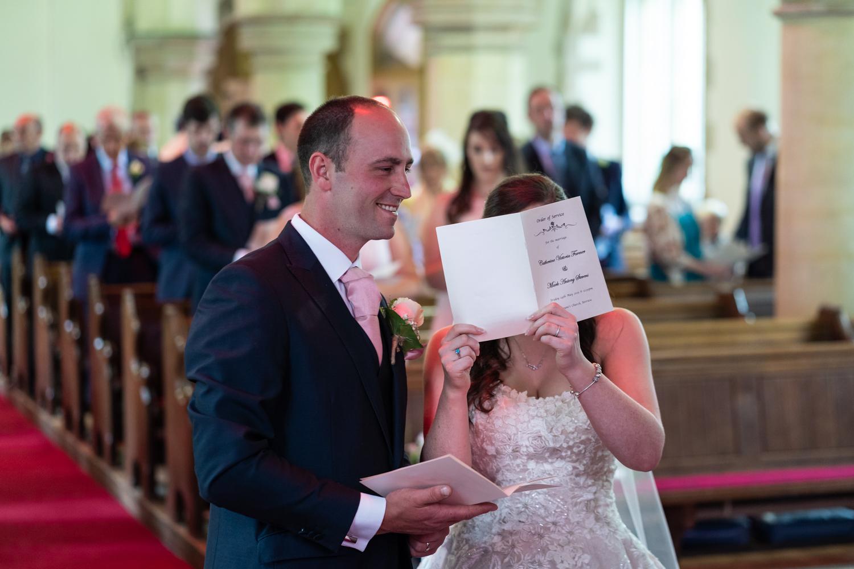 Bride hiding behind order of service