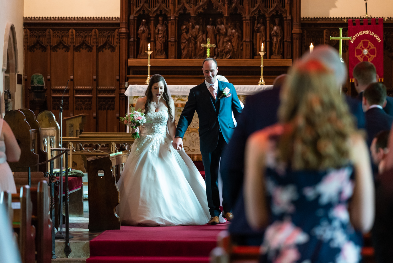 Bride & groom walking down aisle after wedding at church