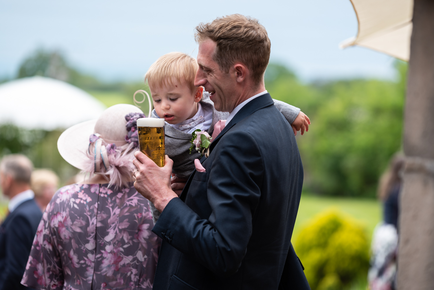 Baby trying to drink beer at wedding