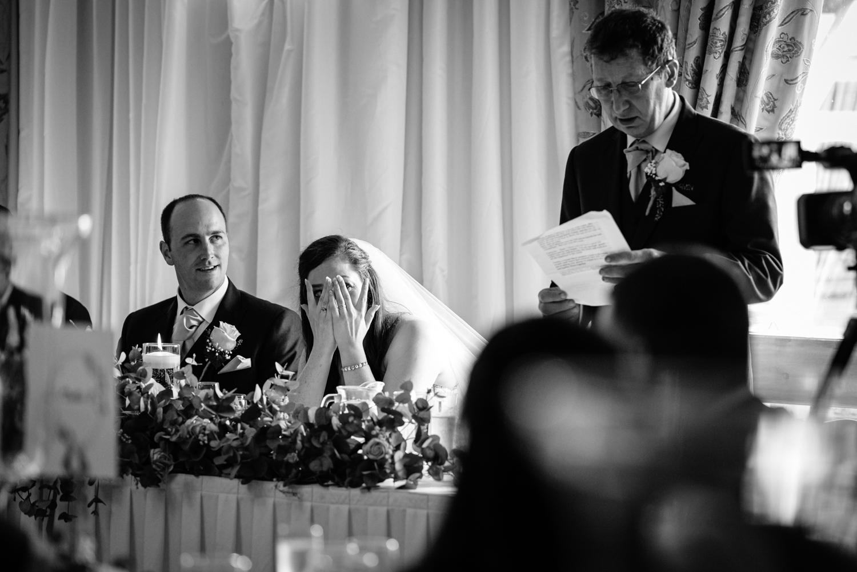 Bride hiding face during wedding speeches