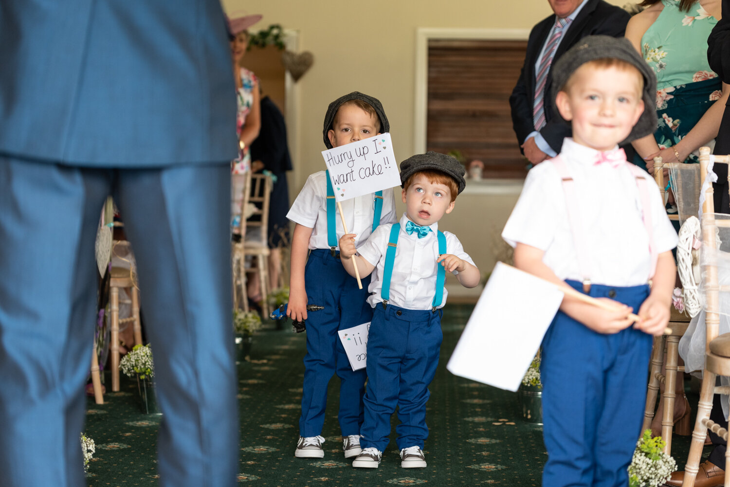 Paige boys walking down the aisle with signs