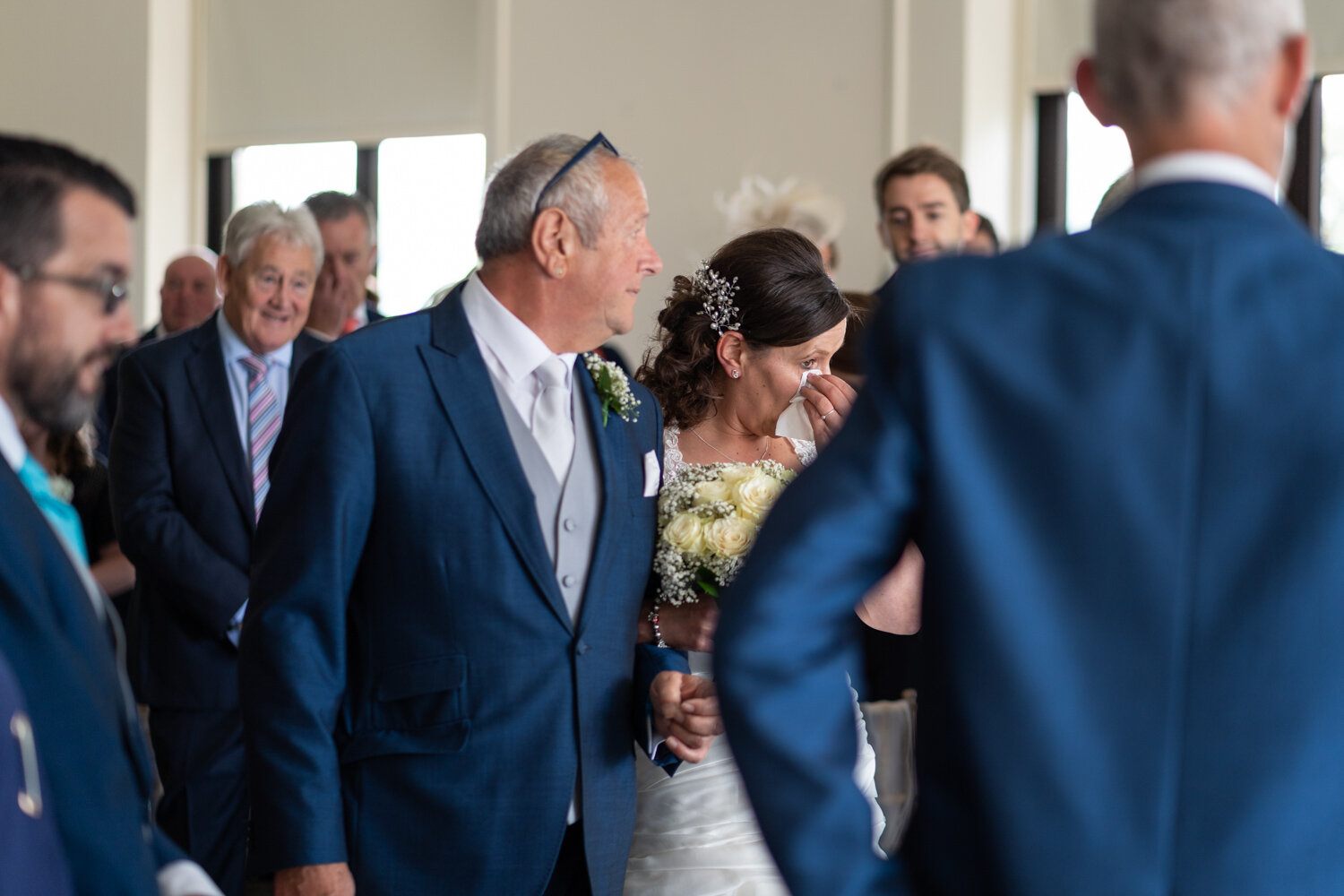 Bride crying with dad walking down the aisle