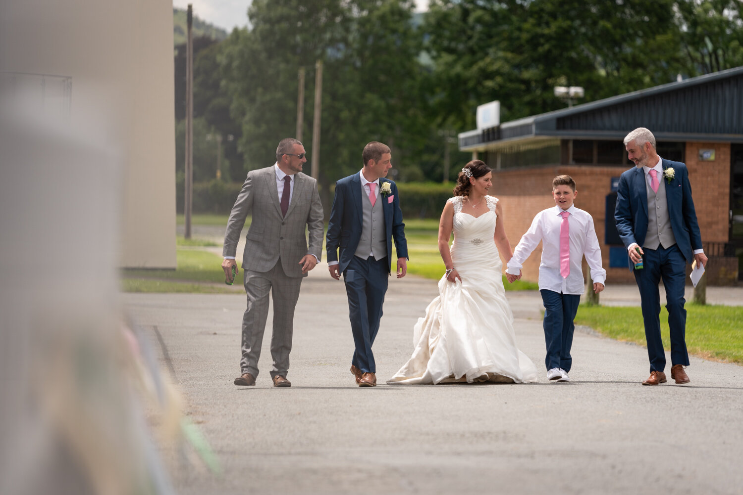Bride, groom and guests walking to ceremony