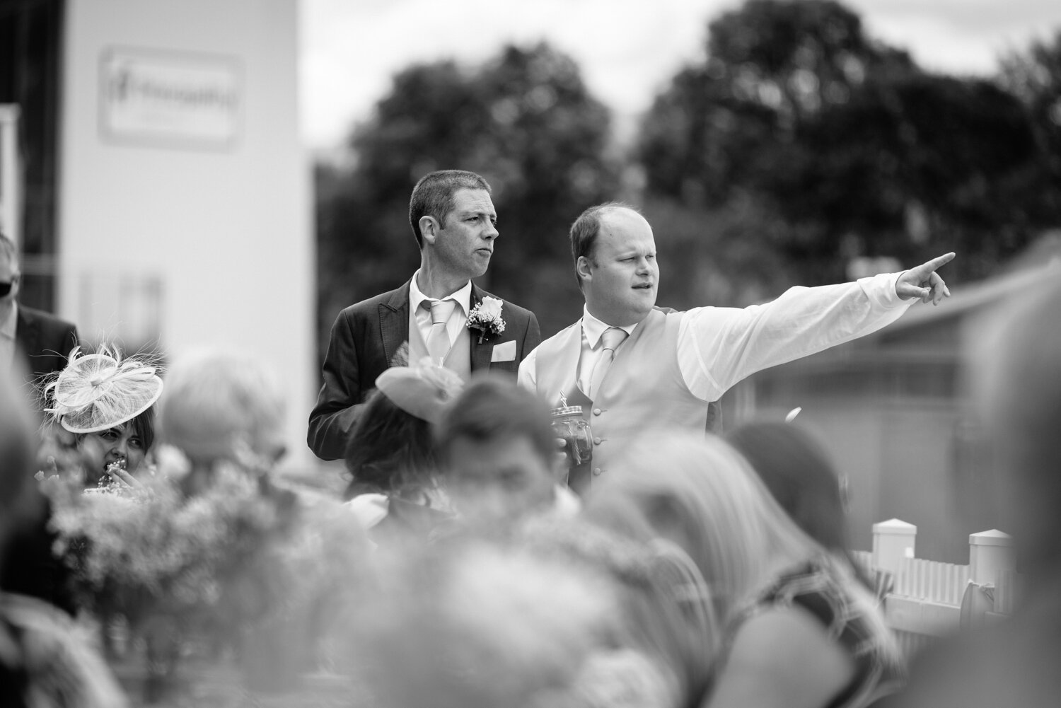 Groom and usher pointing to the distance