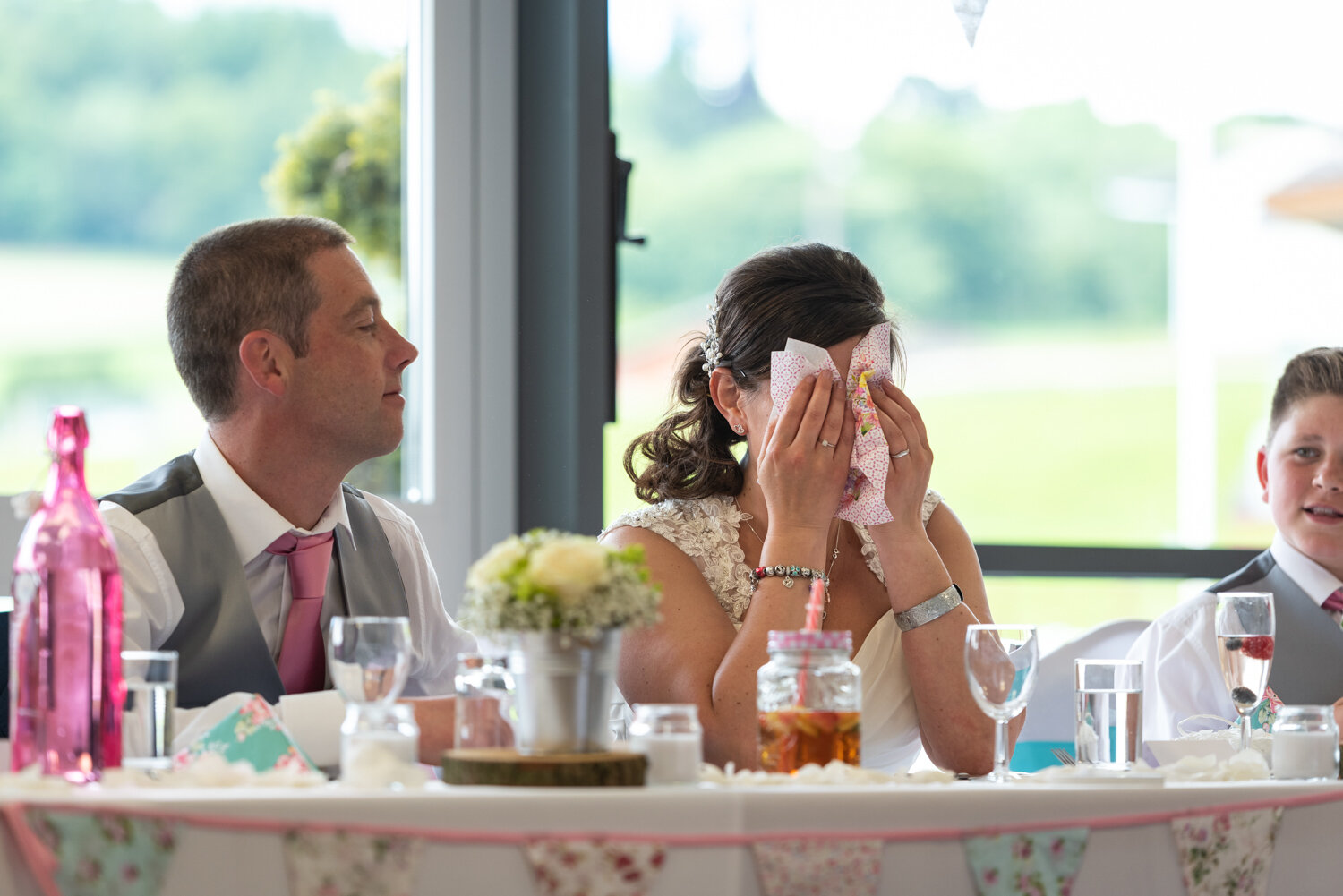 Bride covering her eyes as she cries during speech