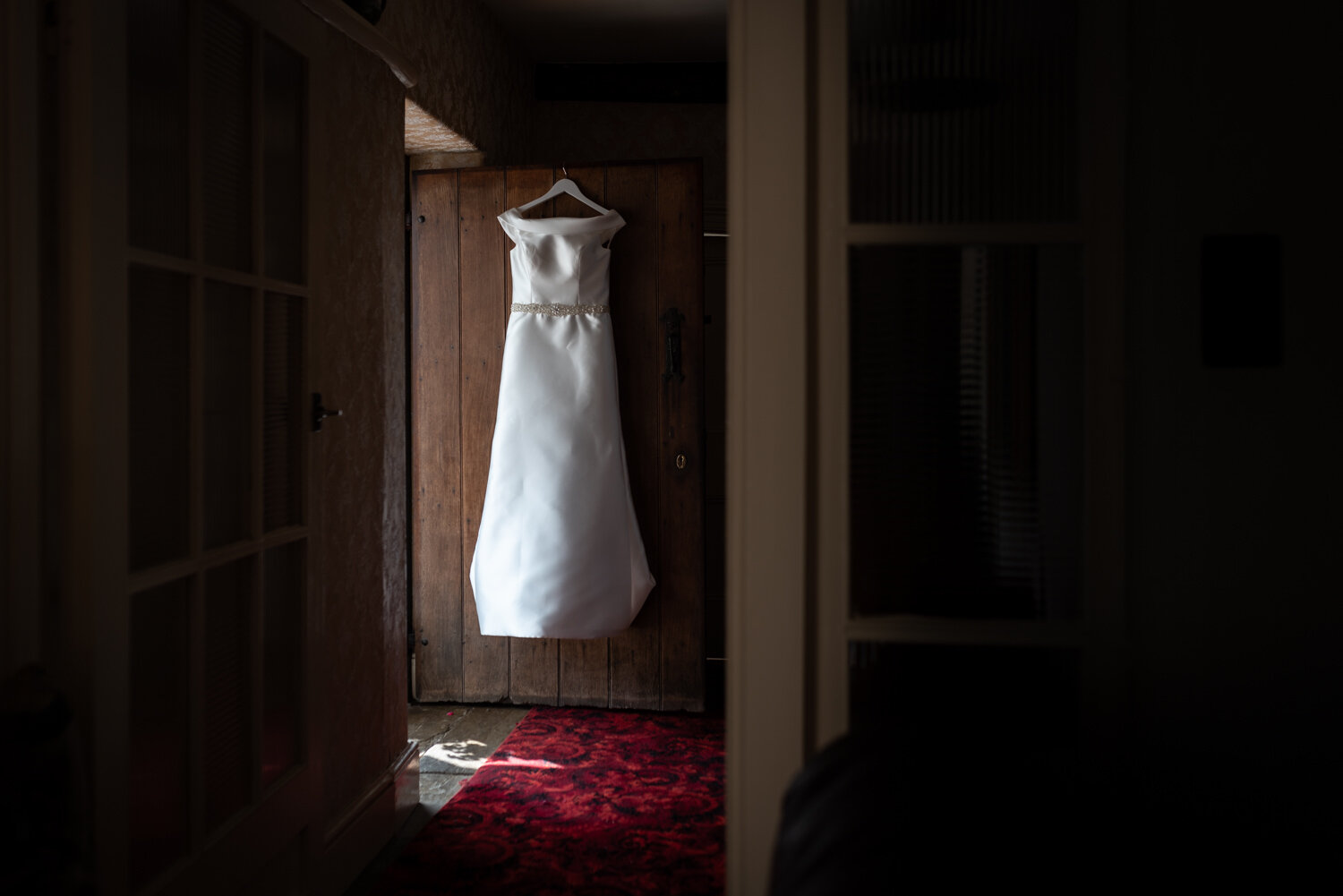 Wedding dress hanging on farmhouse door