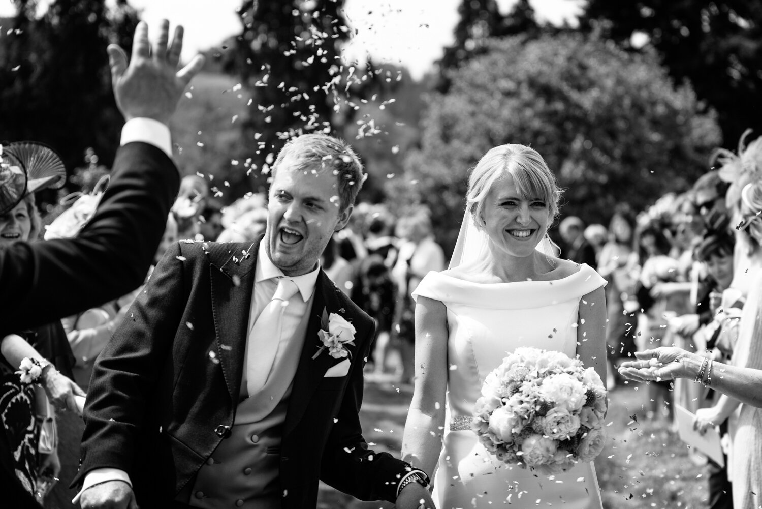 Bride and groom walking through confetti at Glasbury church