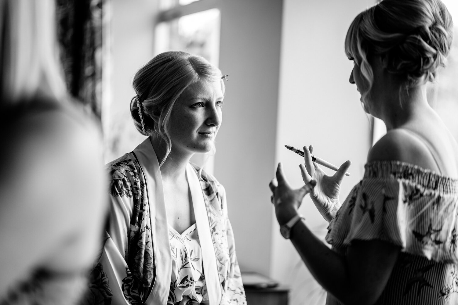 Bridesmaid talking to make-up artist