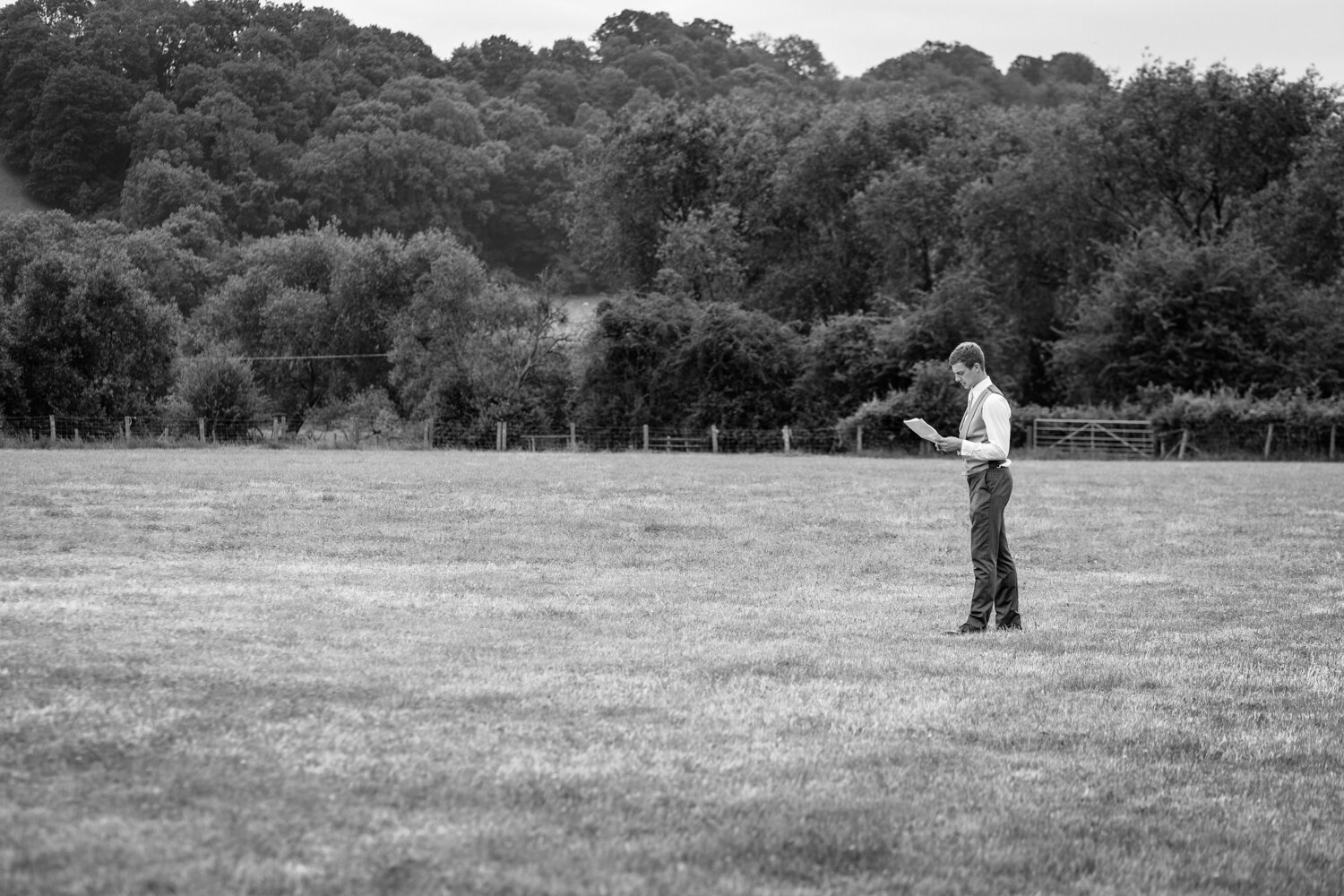 Best man practicing speech alone in field at Powys wedding