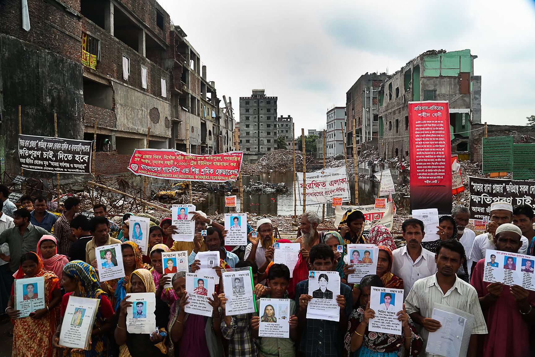 The loved ones of garment workers killed in the Rana Plaza collapse hold photos of the victims in protest (photo:  Jason Motlagh )