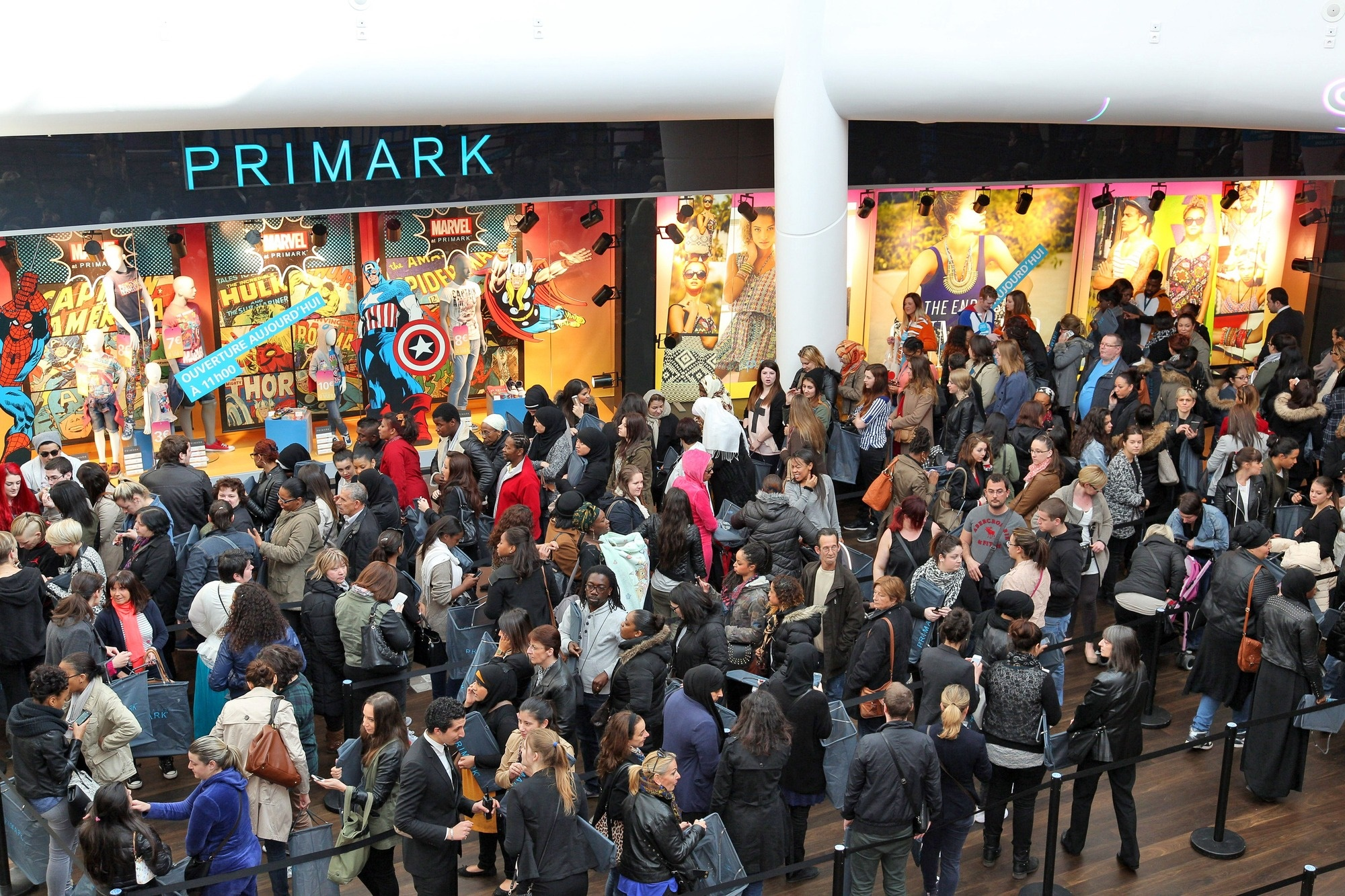 A mob of shoppers outside of a Primark store, enticed by prices as low as  € 3 for a t-shirt (photo:  retail-week.com )